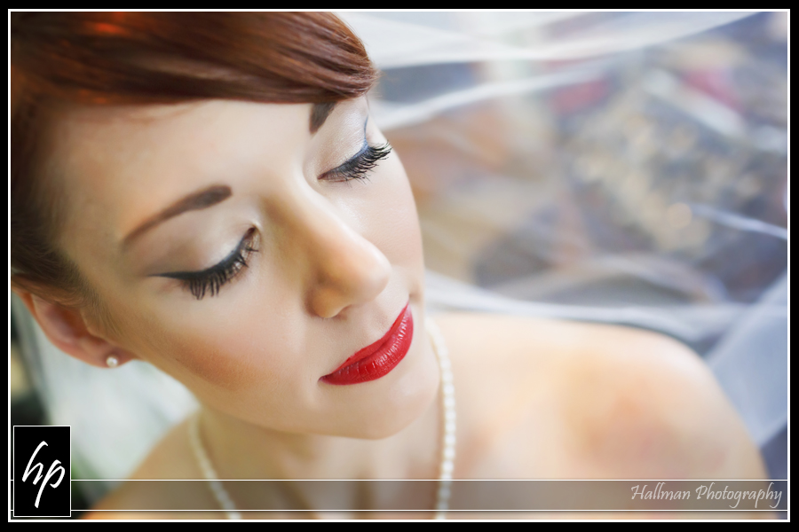 close up of bride's face with makeup done and bright red lipstick