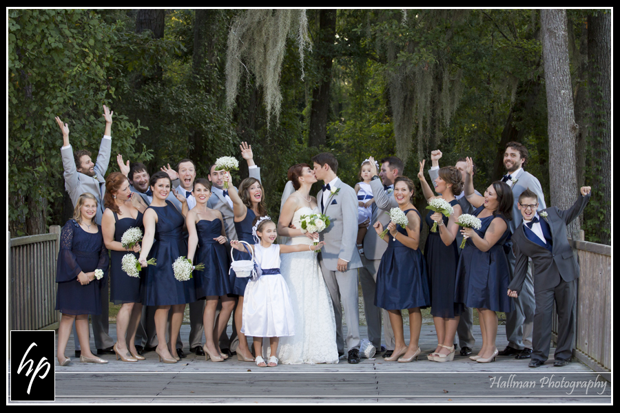 wedding party cheering as bride and groom kiss