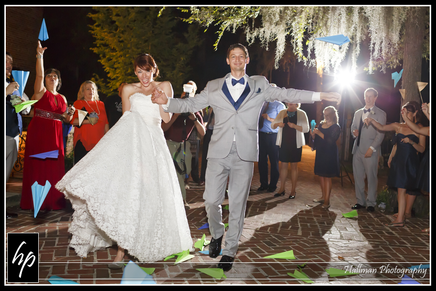 Bride and groom's reception departure with paper airplanes being thrown at them