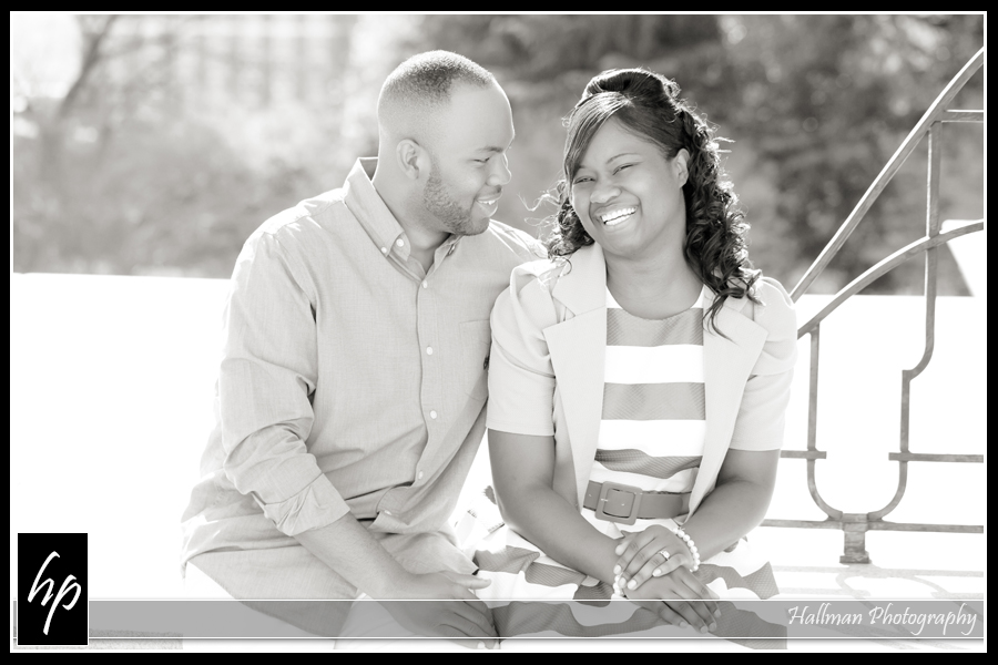 Couple sitting on wall during their engagement portrait session