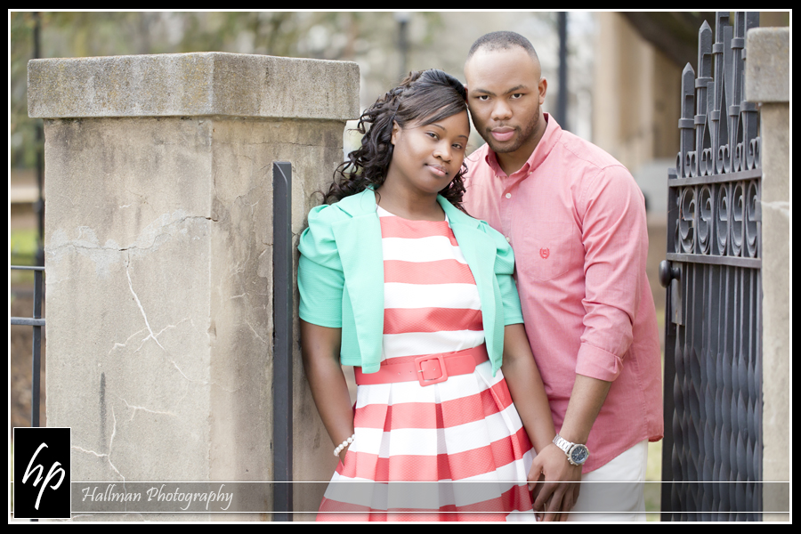 Engaged couple posing against gate during downtown Columbia SC engagement session